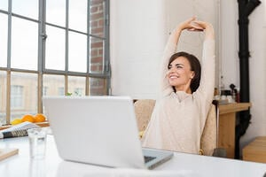 Happy relaxed young woman sitting in her kitchen with a laptop in front of her stretching her arms above her head and looking out of the window with a smile-1