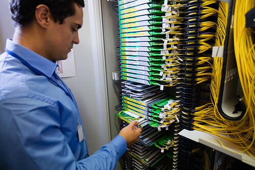 Technician checking routers in server room